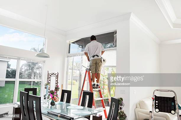 workman on ladder adding tinting to upper, interior window - toned image stock pictures, royalty-free photos & images