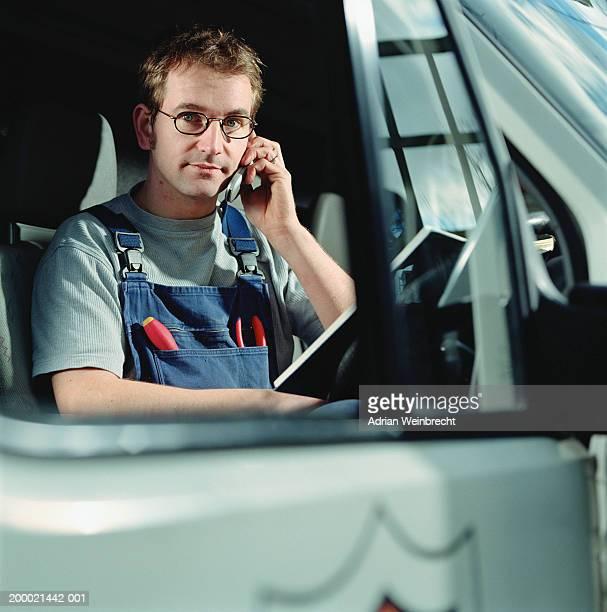 Workman on mobile phone in van, view through open window, portrait