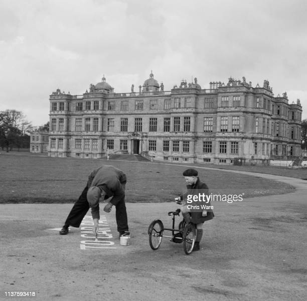 A workman paints a sign directing visitors to the car park at Longleat House the family seat of the Marquess of Bath near Warminster Wiltshire 22nd...