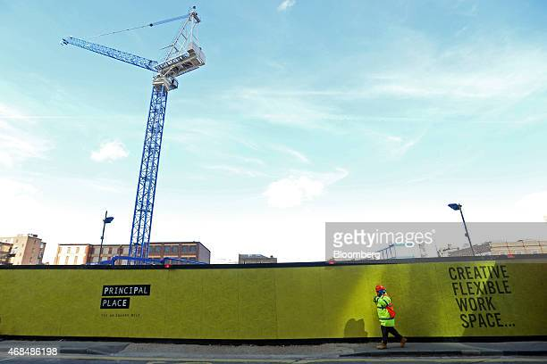 Workman passes a hoarding surrounding the construction site of Principal Place, a joint development by Brookfield Property Partners LP, Concord...