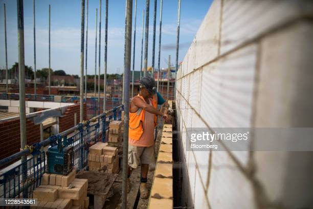 Workman places a brick into position on a residential construction site, operated by Persimmon Plc, in Towcester, U.K., on Wednesday, Sept. 16, 2020....