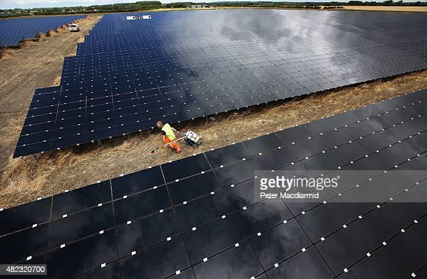 Workman pulls equipment as he cleans panels at Landmead solar farm on July 29, 2015 near Abingdon, England. The 46 megawatt capacity installation was...