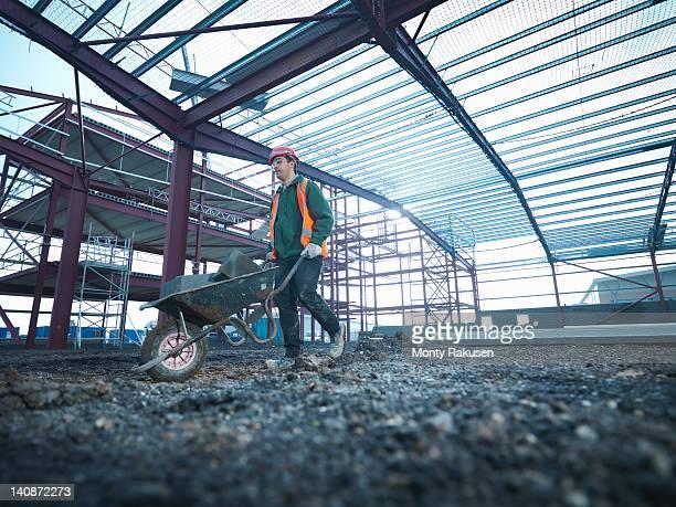 workman pushing wheelbarrow beneath steel construction frame on building site - monty rakusen stock pictures, royalty-free photos & images