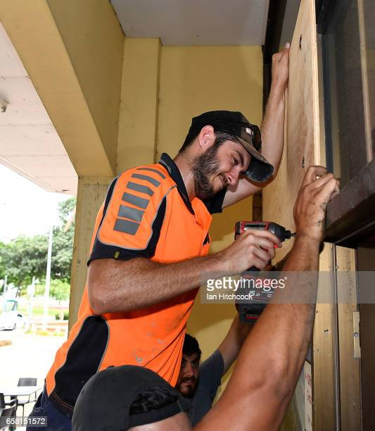 A workman puts up plywood panels to protect a shop on the Strand as residents prepare for Cyclone Debbie on March 27 2017 in Townsville Australia...