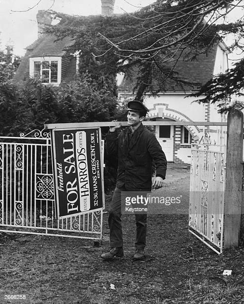 A workman removes the 'For Sale' sign from the house of Dr Savundra former head of the Fire Auto and Marine Insurance Company His newly purchased...