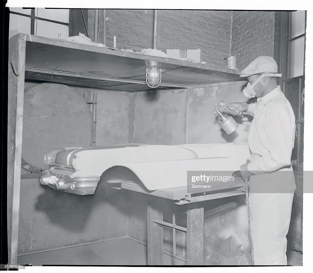 A workman sprays paint on the one-piece fiberglass bodies