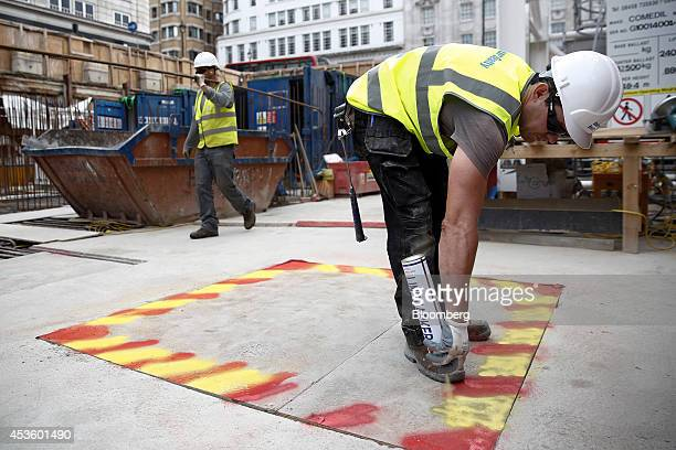 A workman sprays paint to warn of a hazard during building works at Balfour Beatty Plc's St James's Market construction site a joint Crown Estate and...