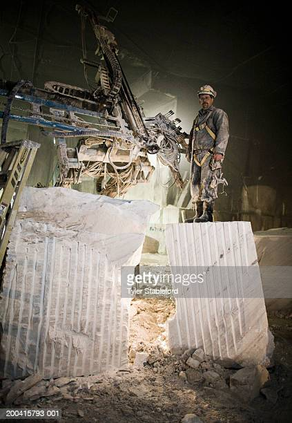 Workman standing by saw in marble quarry