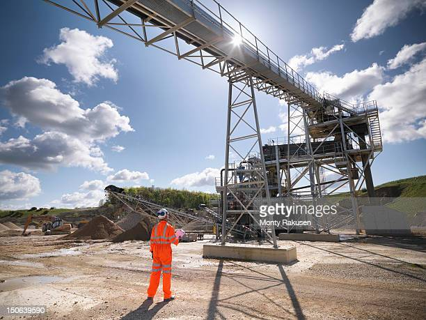Workman standing next to stone screening and crushing machine in quarry