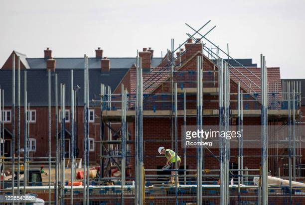 Workman stands among scaffolding poles at a residential construction site, operated by Persimmon Plc, in Towcester, U.K., on Wednesday, Sept. 16,...