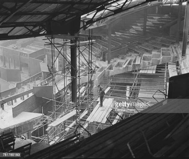 A workman stands on scaffolding surveying the blitz bomb damaged south east stand of the Wimbledon Centre Court during the reconstruction on 9...