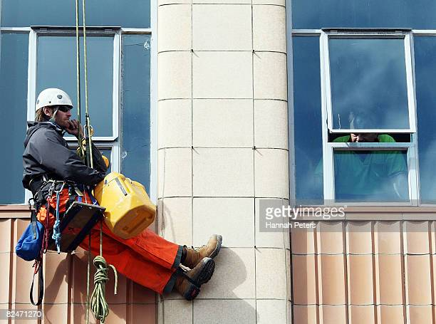 A workman stops work to watch pornstars from the controversial Erotica show ride down Queens Street during the annual 'Boobs on Bikes' parade on...