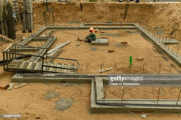 A workman takes a break in the foundation of a house under construction in the Beeler Park neighborhood of Stapleton on August 1 in Denver Colorado...