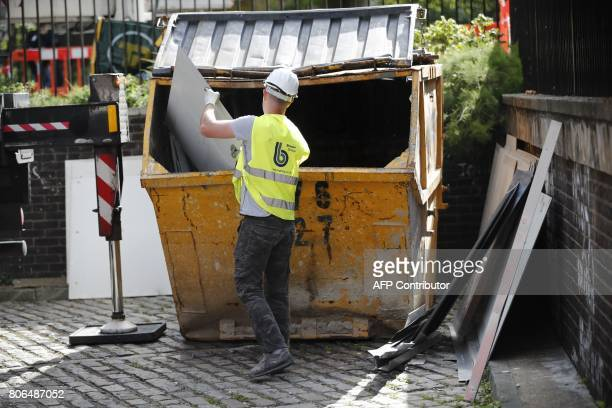 A workman throws a panel of external cladding from the facade of Braithwaite House into a skip in London on July 3 in the wake of the Grenfell Tower...