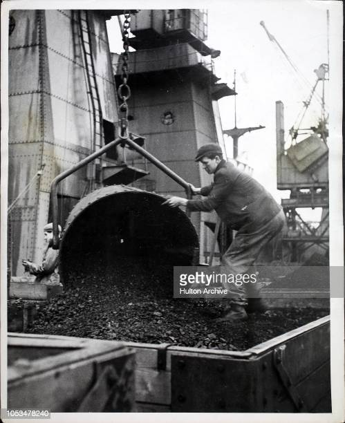 A workman tips out a skip of American coal which has been unloaded by crane from a ship at Cardiff docks Wales About one third of the coal to be...