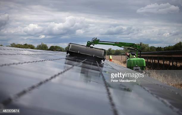 Workman uses a machine to clean panels at Landmead solar farm on July 29, 2015 near Abingdon, England. The 46 megawatt capacity installation was the...