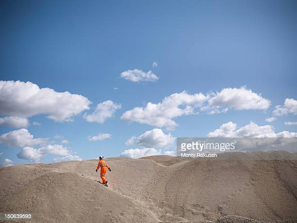 Workman walking on crushed and sorted stone in quarry