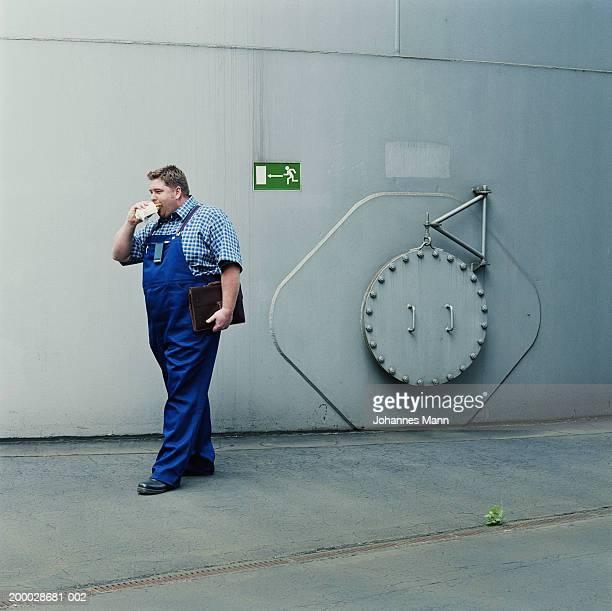 workman walking outside power station, eating snack - combinaison de protection photos et images de collection