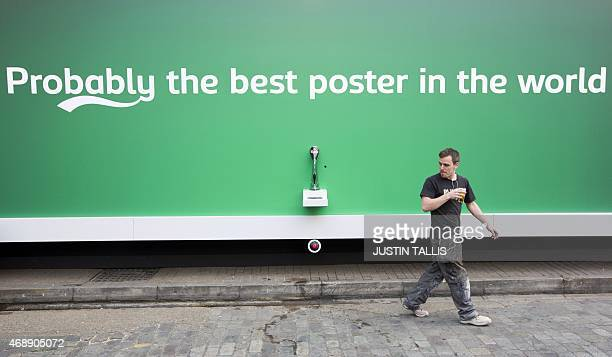 A workman walks away with a beer that he poured himself from a billboard poster with a built in tap that is dispending free beer outside the Truman...