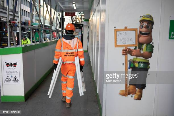 Workman walks past an illustration of a construction worker holding a sign which reads 'vote Labour' on 21st January 2020 in London England United...