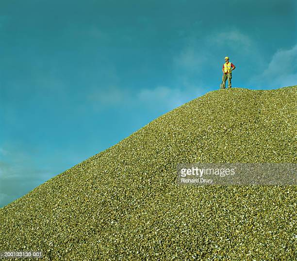workman wearing hard hat and reflective coat on top of heap of gravel - richard drury stock pictures, royalty-free photos & images