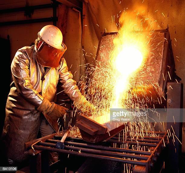 Workman wearing safety mask, melting scrap metal