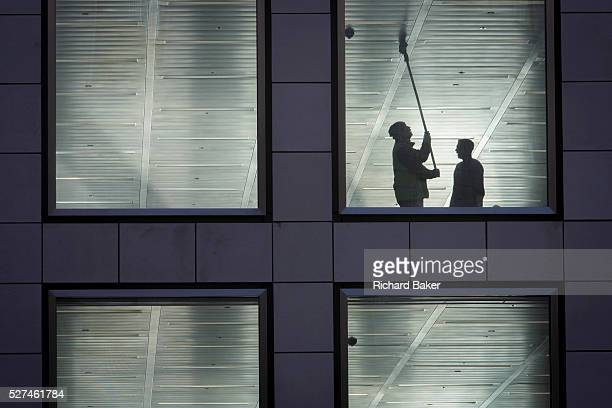 A workman wipes the ceiling of a vacant office building in the City of London With a supervisor alongside the worker reaches high above his head the...