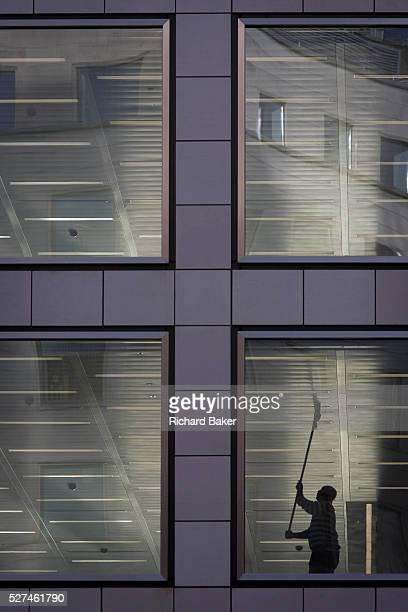 A workman wipes the ceiling of a vacant office building in the City of London Reaching high above his head the man uses a squeegeetype mop to clean...