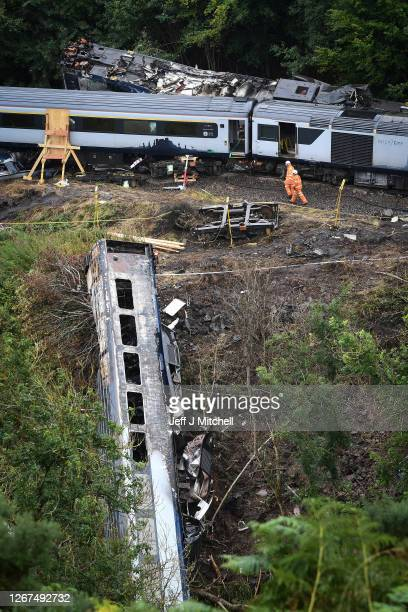Workmen are seen at the site of last week's train derailment on August 21 2020 in Stonehaven Scotland The train derailed last week after hitting a...