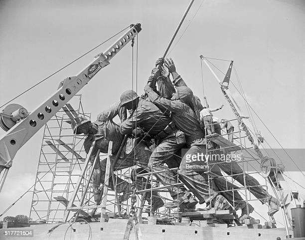 Workmen are shown putting the finishing touches on the Iwo Jima statue which will be on the Virginia side of the Potomac River The heavy rifle of a...
