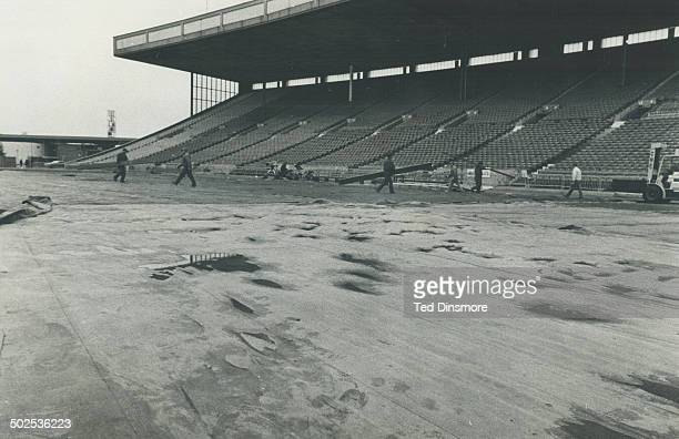 CNE workmen begin peeling back a soggy tarpanlin at the stadium this morning in preparation for this afternoon's eastern conference final between the...