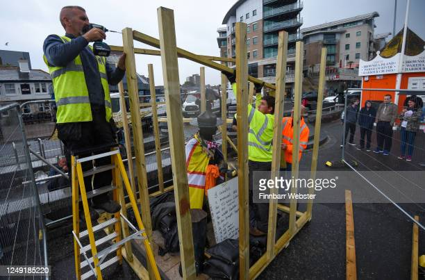 Workmen board up the Lord Baden-Powell statue on June 12, 2020 in Poole, United Kingdom. The statue of Robert Baden-Powell on Poole Quay is to be...