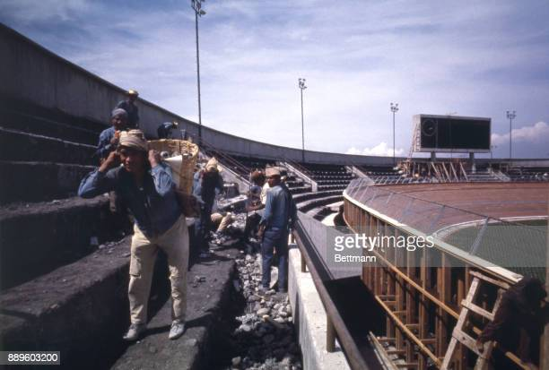 Workmen carry baskets of construction rubble from grandstand area of the Velodrome where cycling events will be held during the 1968 summer Olympics