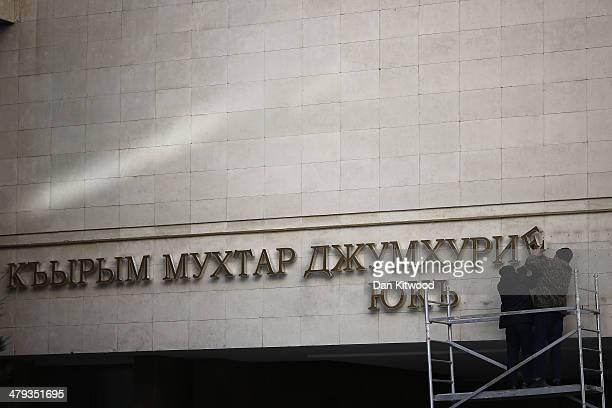 Workmen change the lettering on the Parliament building to a sign that reads 'Crimean Autonomous Council' on March 18 2014 in Simferopol Ukraine...