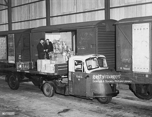 Workmen check goods as they are loaded onto a British Railways mechanical horse.