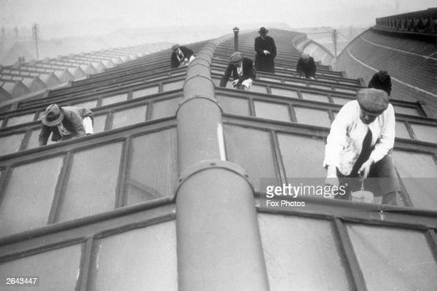 Workmen cleaning and painting along a stretch of glass roofing at York Station.