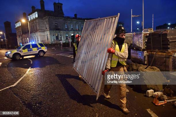 Workmen clear debris from the roadside after Storm Eleanor damaged an office construction site on January 3 2018 in Belfast Northern Ireland The Met...