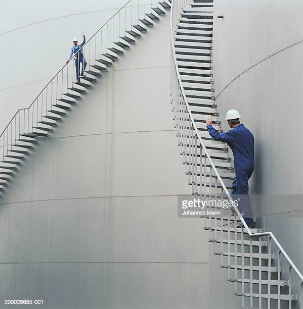 Workmen climbing walkways outside power station, waving to one another