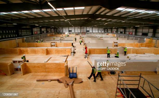 Workmen construct spaces for hundreds of beds in the indoor training centre at parc y Scarlets in Llanelli, south Wales on March 30 as life in...