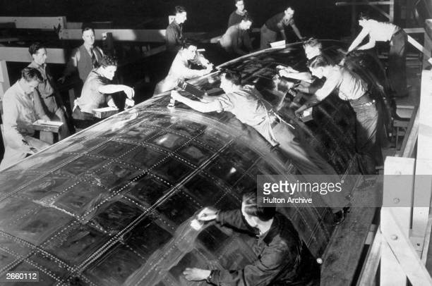 Workmen covering the seams in the body of a Boeing Stratoliner aeroplane with soap to test that every joint is properly sealed at the Boeing factory...