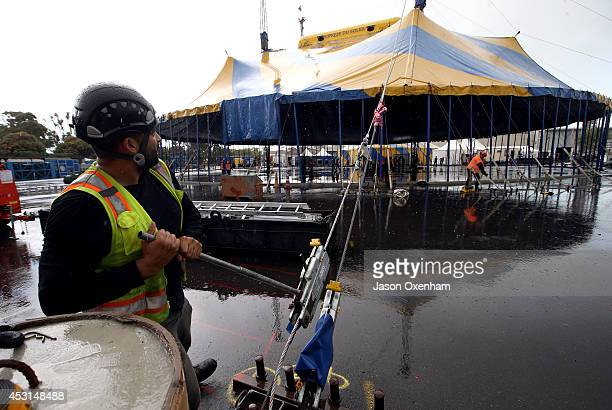 Workmen erect more than 100 supporting poles to bring the canvas of the Cirque Du Soleil tent up during a heavy rain storm at Alexandra Park on...