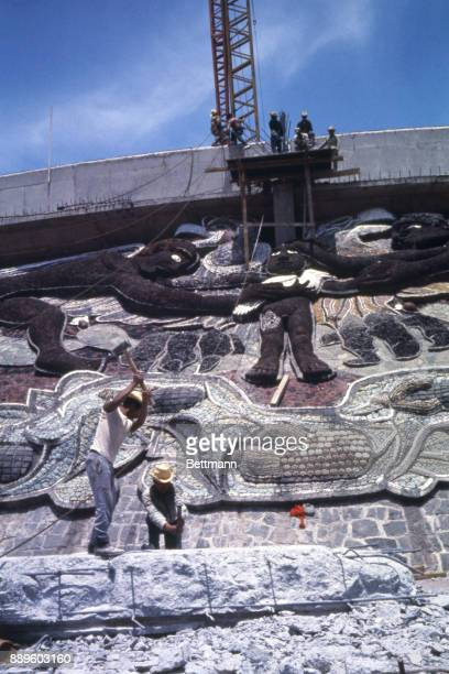 Workmen erect pedestal for the Olympic torch above a mosaic on the side of the Olympic Stadium at the University of Mexico Torch will be lighted...