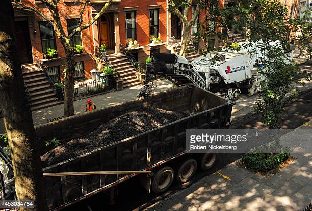 Workmen from a road construction crew guide a road milling machine July 21 2014 down a street in the Brooklyn borough of New York City The work...