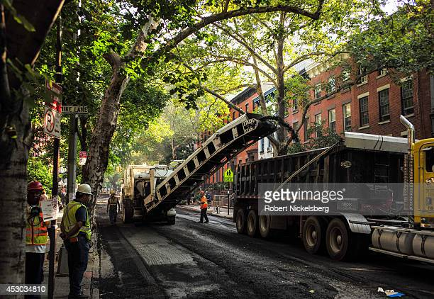 Workmen from a road construction crew guide a road milling machine July 22 2014 down a street in the Brooklyn borough of New York City The work...