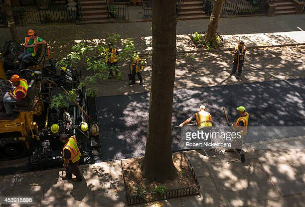 Workmen from a road construction crew repave a residential street with asphalt July 30 2014 in the Brooklyn borough of New York City