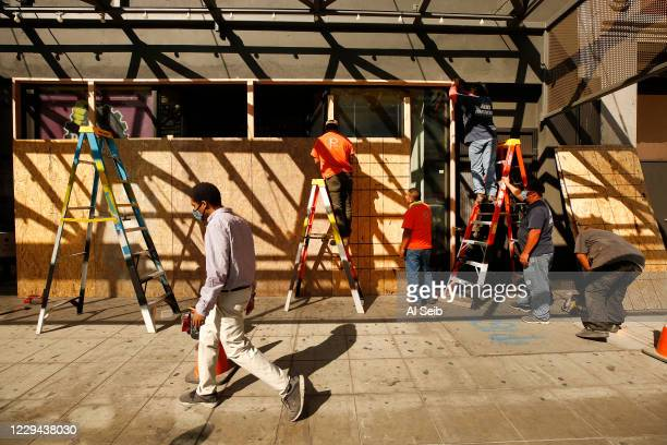 Workmen from RDG Construction build a plywood wall at the storefront of Planet Fitness on South Broadway in downtown Los Angeles to keep intruders...