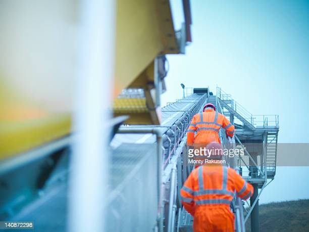 Workmen in reflective clothing climbing steps of screening conveyor at quarry
