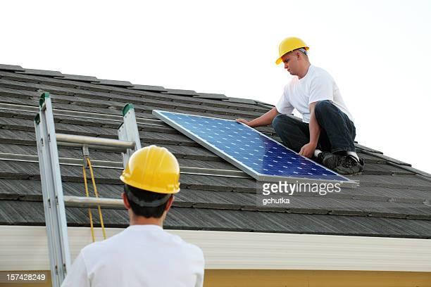 Workmen installer un panneau solaire
