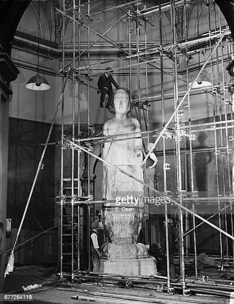 Workmen installing the colossal Amitabha Buddha in the Central Hall at Burlington House in readiness for the Royal Academy's International Exhibition...