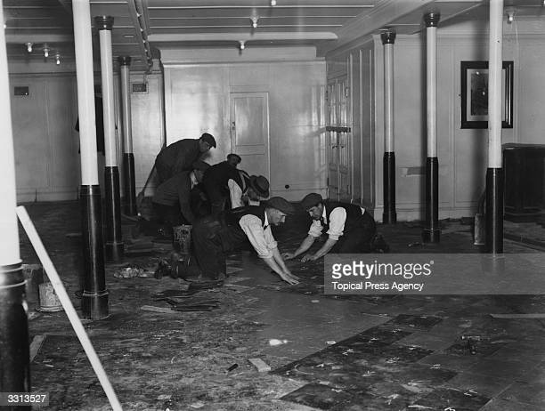 Workmen laying a linoleum floor in the third class dining room of the liner 'Berengaria'.